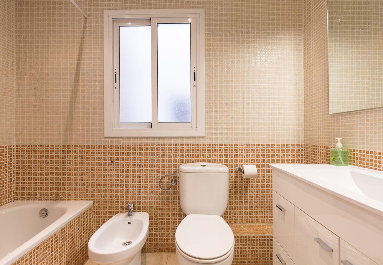 cuarto de baño con bañera, completo, práctico en la casa plaza españa barcelona